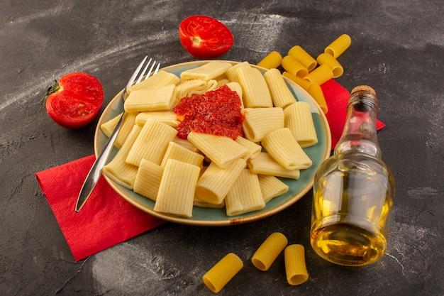 正面図は灰色のテーブルパスタイタリア料理の食事でプレート内のトマトソースとイタリアのパスタを調理