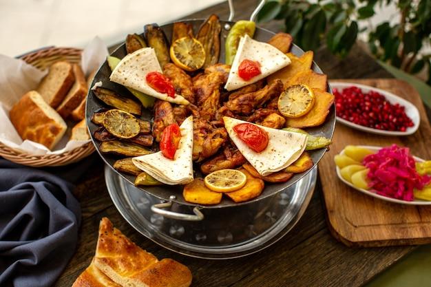 Вид спереди приготовленных мясных овощей вместе с кусочками хлеба и гранатом на коричневом столе