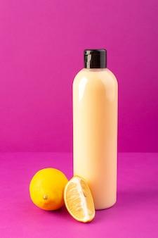 Вид спереди кремового цвета, бутылка пластиковая, в виде шампуня, с черной крышкой и лимонами на фиолетовом фоне.