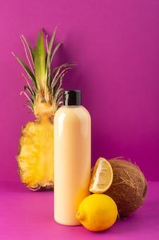 Вид спереди кремового цвета в пластиковой бутылке с шампунем и черной крышкой с лимонами, ананасом и кокосовым орехом на фиолетовом фоне