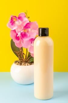 Вид спереди кремового цвета, бутылка пластиковая, в виде шампуня с черной крышкой, изолированная вместе с цветами на желто-голубом фоне косметика для красоты волос
