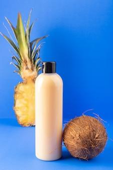 Вид спереди кремового цвета, бутылка пластикового шампуня с черным колпачком, изолированная вместе с нарезанным ананасом и кокосом на синем фоне.