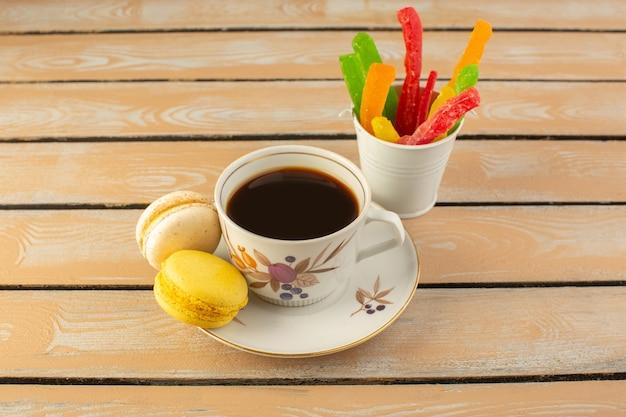 クリーム色の素朴なデスクにフレンチマカロンとマーマレードがあり、コーヒーの写真が強く、強くて強いコーヒーの正面図カップ