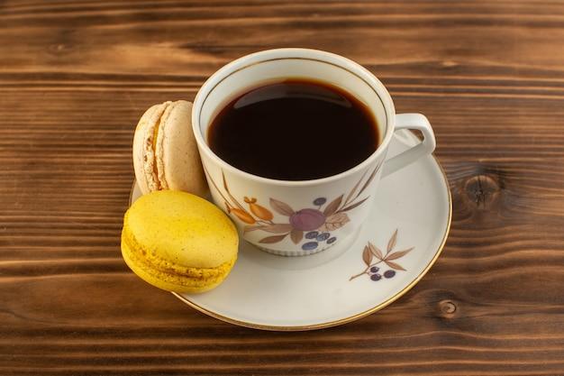 茶色の木製の素朴なデスクコーヒーホットドリンクにフレンチマカロンとホットで強いコーヒーのフロントビューカップ