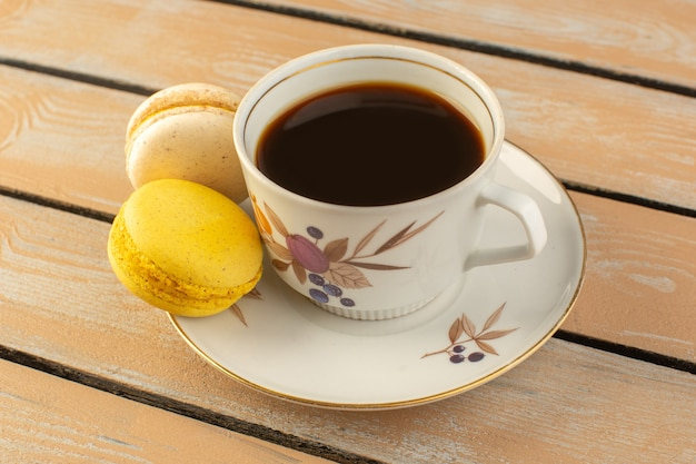 Чашка горячего и крепкого кофе, вид спереди, с французскими макаронами на кремовом деревенском столе пить кофе крепкий