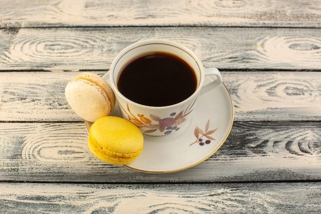 Чашка горячего и крепкого кофе, вид спереди, с французскими макаронами на сером деревенском столе, горячий напиток с кофе