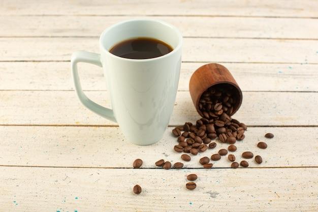 Чашка кофе в белой чашке, вид спереди, со свежими коричневыми кофейными семечками на светлой поверхности, пить кофе, кофеин