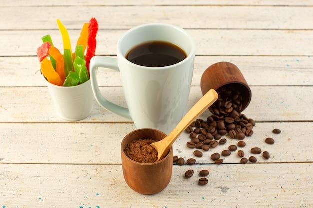 明るい表面のコーヒーカフェインに新鮮な茶色のコーヒーの種子と白いカップでコーヒーの正面図カップ