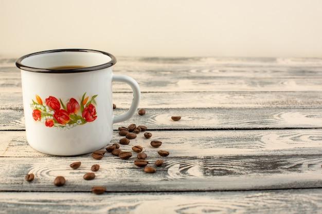 Чашка кофе с коричневыми кофейными семечками на сером деревенском столе, вид спереди, напиток кофейного цвета