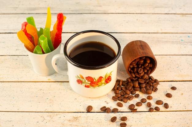 Чашка кофе, вид спереди со свежими коричневыми кофейными семечками и мармеладом на светлой поверхности, пейте кофе с кофеином