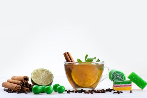 Чашка чая, вид спереди с конфетами, лимоном и мармеладом на белом, десертные конфеты