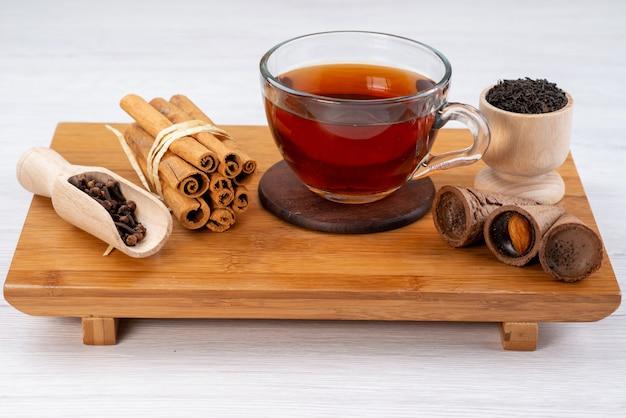 Чашка чая с корицей и рожками на коричневых деревянных десертных конфетах, вид спереди
