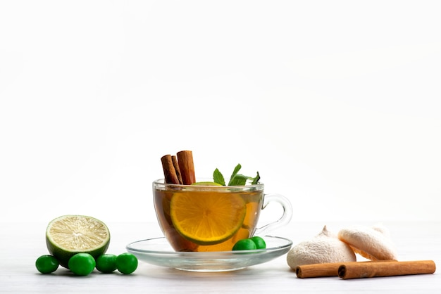 Чашка чая, вид спереди с лимонными конфетами и печеньем на белом, чайные десертные конфеты