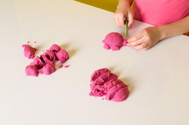 화려한 운동 모래와 함께 연주 분홍색 티셔츠에 전면보기 귀여운 사랑스러운 소년