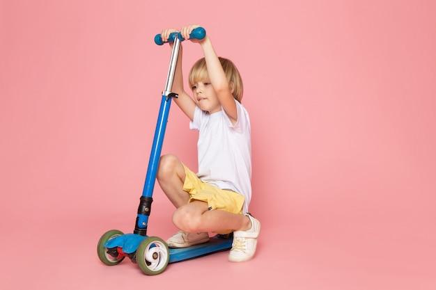 Вид спереди милый мальчик в белой футболке и желтых джинсах верхом на самокате на розовом пространстве