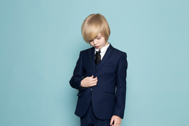 Вид спереди милый деловой мальчик в синем классическом костюме позирует бизнес работа моды