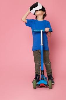 Вид спереди милый ребенок мальчик в синей футболке верхом на самокате на розовом полу