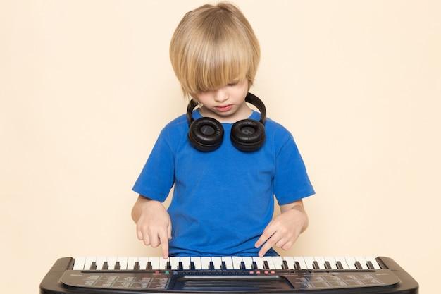 Вид спереди милый маленький мальчик в синей футболке с черными наушниками играет маленький милый пианино