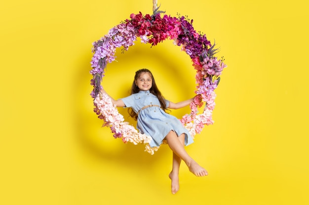 正面のかわいい子供は青いドレスを着て微笑み、花のブランコに座っています。