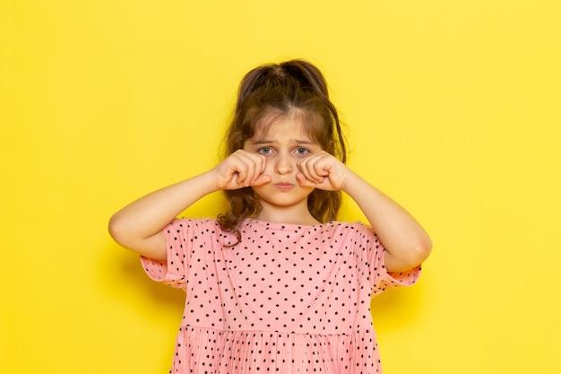 Вид спереди милый маленький ребенок в розовом платье фальшиво плачет