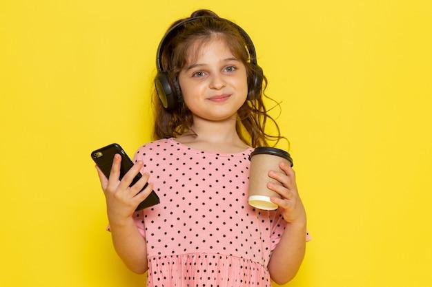 スマートフォンとコーヒーカップを保持しているピンクのドレスで正面かわいい子供