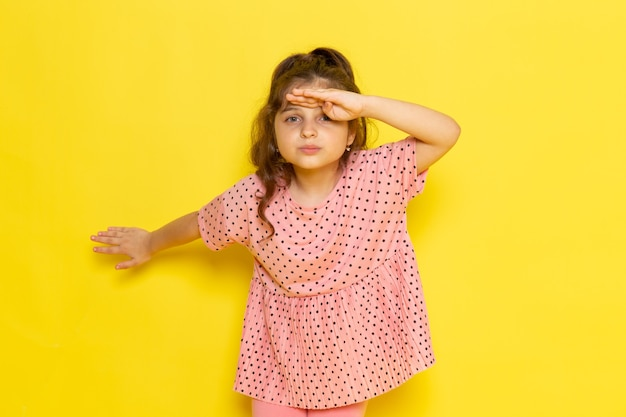 遠くを見ているピンクのドレスで正面のかわいい子供