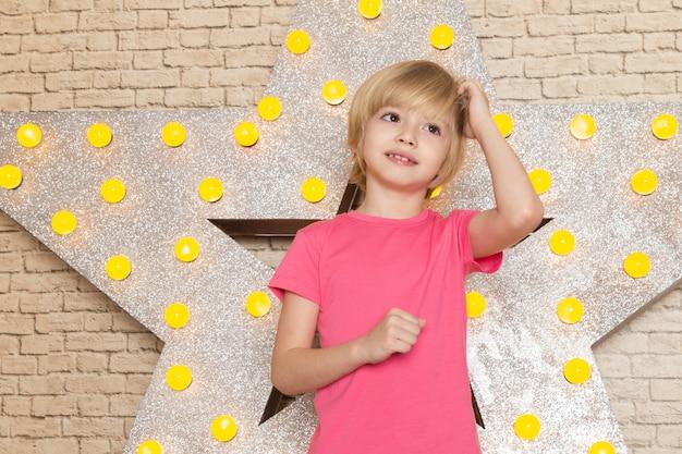 星にピンクのtシャツグレージーンズで正面のかわいい子供設計された黄色のスタンドと明るい背景