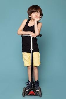 Вид спереди милый думающий мальчик в черной футболке верхом на самокате на голубом пространстве