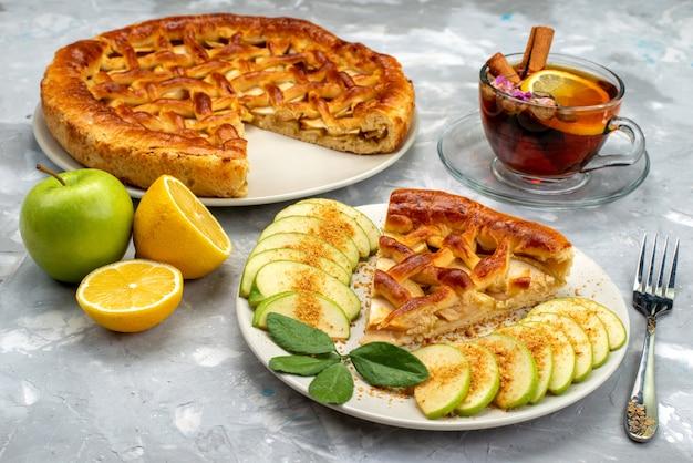 Вид спереди восхитительный яблочный торт внутри тарелки с чаем и свежим зеленым яблоком на деревянном столе, торт, бисквитный сахар