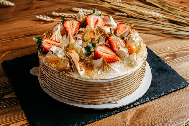 Вид спереди вкусный торт ко дню рождения украшенный вкусной клубникой круглый внутри белой тарелки сладкое печенье на день рождения на коричневом фоне