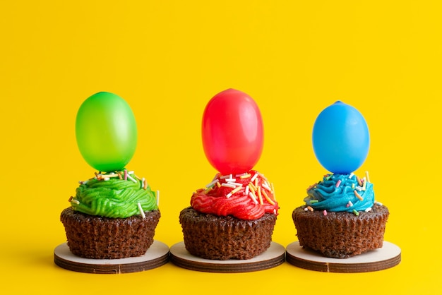 Вид спереди восхитительные шоколадные пирожные с конфетами и шариками на желтом, конфетном бисквитном цвете