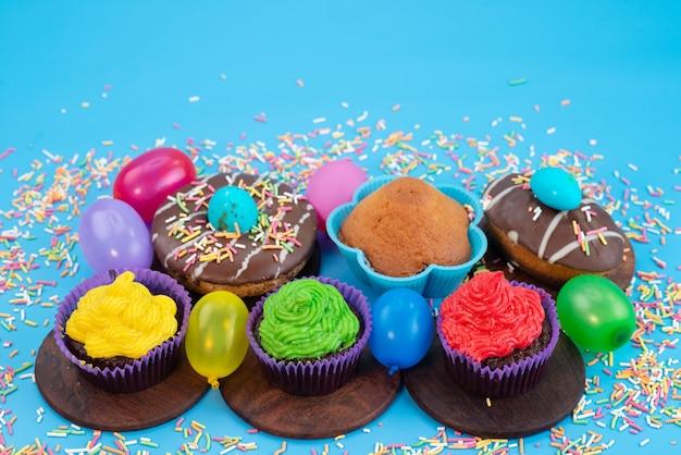 Вид спереди восхитительные шоколадные шоколадные пирожные с конфетами, пончиками и шариками на синем, конфетном бисквитном цвете