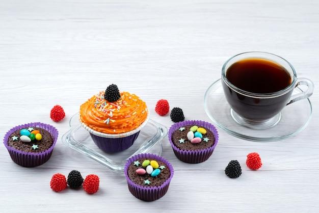 Вид спереди восхитительных пирожных внутри фиолетовых форм вместе с чашкой чая на белых конфетах конфетного цвета.