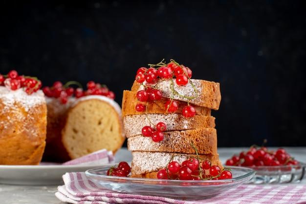 白いデスクケーキビスケットティーベリーシュガーの新鮮な赤いクランベリーと正面のおいしいケーキ