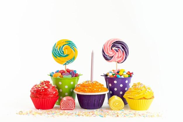 Вид спереди восхитительные торты с красочными конфетами и мармеладом на белом, сахарном цвете бисквитного торта