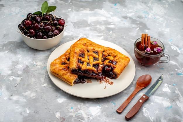 正面のおいしいチェリーケーキとフルーティーな内部の白い皿にチェリーとダークデスクケーキビスケットフルーツのお茶