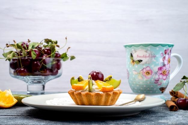 グレーとブルーのデスクのフルーツケーキビスケットにシナモンティーと一緒にクリームと新鮮なスライスフルーツが入った正面のおいしい小さなケーキ