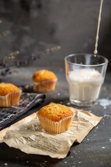 グレーのテーブルクッキーティービスケット甘いに正面に紫の花と牛乳のおいしい小さなケーキ