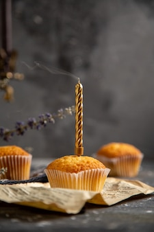 灰色のテーブルクッキーティービスケット甘い砂糖に紫の花と正面のおいしい小さなケーキ