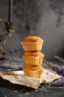 グレーのテーブルクッキーティービスケット甘い上に紫色の花と正面のおいしい小さなケーキ