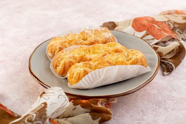 Вид спереди вкусные длинные торты с бумажным пакетом внутри тарелки на розовом столе