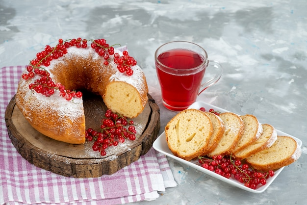 白いデスクケーキビスケットティーベリーシュガーの新鮮な赤いクランベリーとクランベリージュースと正面のおいしい丸いケーキ