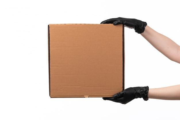 Фронтальный вид доставки коробка держится женской рукой в черных перчатках на белом столе