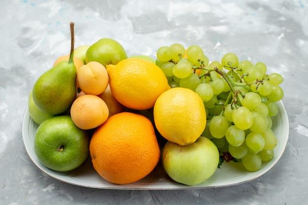 Вид спереди разные фрукты, такие как лимоны, груши, яблоки, виноград и апельсины на белом столе внутри тарелки, цвет фруктов, витамин, лето