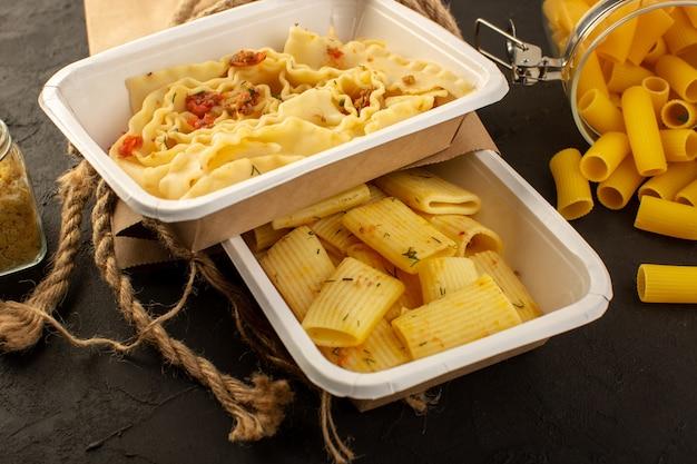 Мука из теста с сушеными зелеными травами в белых мисках и упаковка вместе с сырой итальянской пастой на темном фоне.