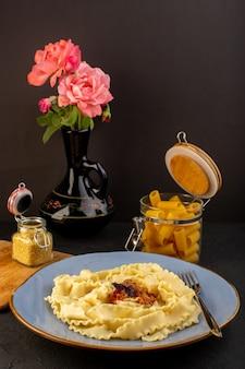 正面図の生地パスタは、丸い青いプレートの内側に美味しい塩を入れて調理し、デザインされたカーペットの上に水差しの内側に花をつけ、暗い机でイタリア料理を調理します