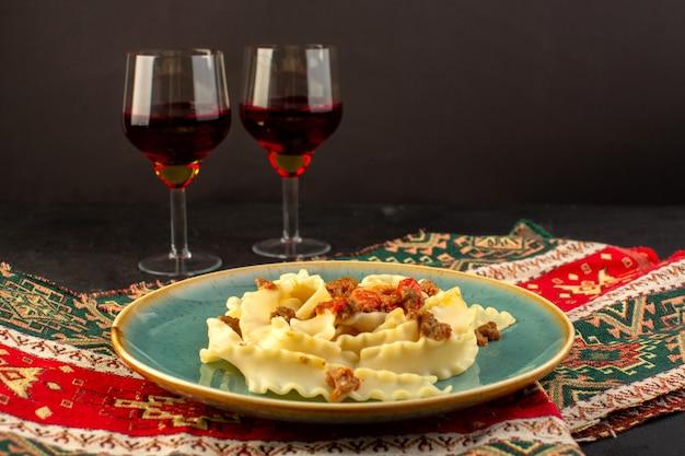 Макароны из теста, приготовленные с видом спереди, вкусные, соленые, на круглой зеленой тарелке с бокалами вина на ковре и темном столе
