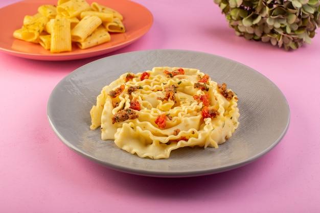 분홍색에 회색 접시 안에 요리 썰어 야채와 고기와 함께 전면보기 반죽 파스타