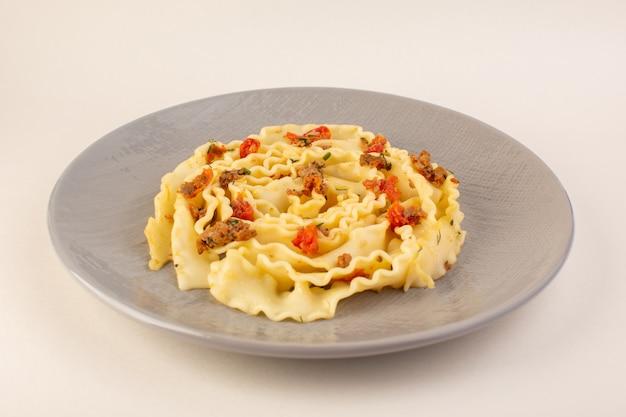 調理されたスライス野菜と白地にグレーのプレートの中の肉の正面生地パスタ