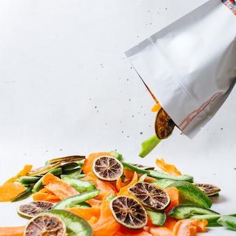 Вид спереди кусочки сушеных фруктов внутри и снаружи небольшого бумажного пакета на белом